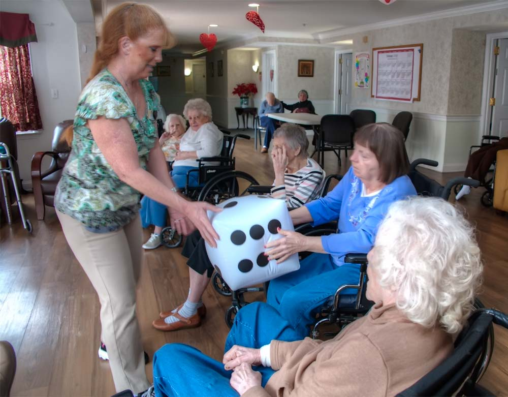 Aide-handing-dice-balloon-to-resident-in-wheelchair