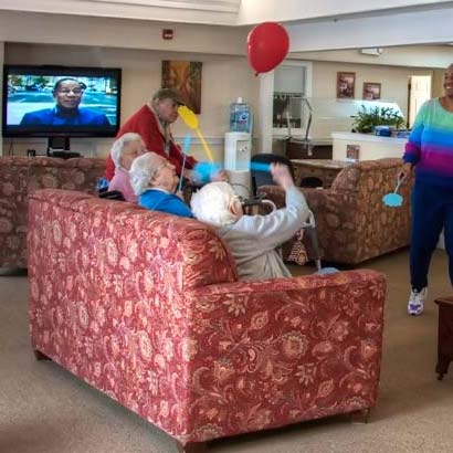 Residents tossing balloon in community room while sitting on a couch