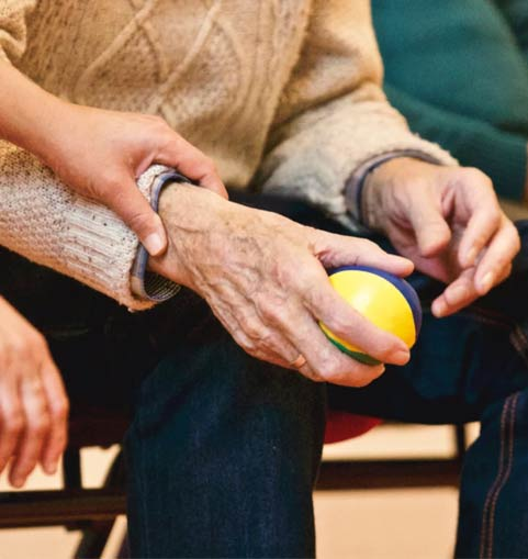 Elderly man holding a small ball in his hand as younger womans hand holds his wrist